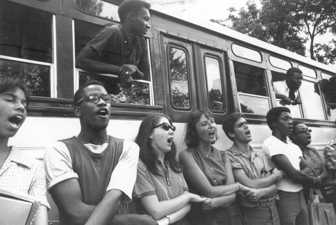 Freedom Summer volunteers sing, hand-in-hand, next to a bus